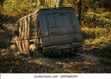 Ofroad for hard man. Off road car going through mud in forest. SUV stuck on country road with nature on background. Dirty offroad car needs help. Adventure, extreme driving and challenge concept