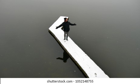 OGGIONO, ITALY - CIRCA MARCH 2018:  a man stands on a snowy wooden pier on the lake Oggiono,  a mere close to lake Como, Lombardy, Italy