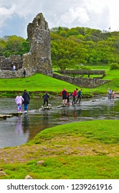 Ogmore, Bridgend County Borough / Wales UK - 5/12/2018 : Ogmore Castle is on the banks of the river Ewenny in South Wales. Here a young family & their dog cross the river via ancient stepping stones.