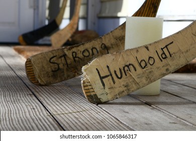 Ogunquit, Maine, USA: April 10, 2018: Hockey sticks surround and candle on a porch in a tribute to the Canadian hockey team killed in a bus crash in Saskatchewan, Canada.