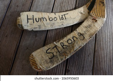 "Ogunquit, Maine, USA: April 10, 2018: Hockey sticks with the words "" Humboldt Strong"" handwritten on the tape that wraps around the blades. A memorial in support for the Humboldt Broncos hockey team,"