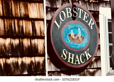 """Ogunquit, Maine, USA: April 20, 2018: A closeup shot of a rustic wooden sign on a weathered wood shingled restaurant that says """"Lobster Shack"""" in Perkins Cove, Maine.  Maine is known for its seafood."""