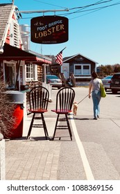 Ogunquit, Maine, USA: April 25, 2018: a women walking her dog on a sunny day in Perkins Cove by a local seafood restaurant open for business with outside seating.
