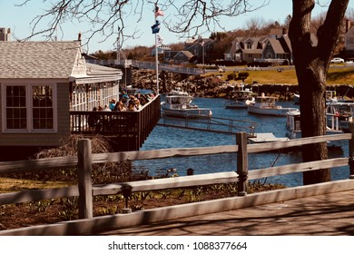 Ogunquit, Maine, USA: April 25, 2018: People dining on an outside deck overlooking Perkins cove on a sunny spring day. Perkins Cove is a very scenic and popular area for tourists.