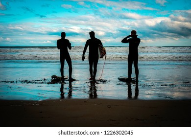 Ogunquit, Maine USA: November 10th, 2018: three silhouettes of Maine surfers preparing to enter the ocean with storm waves and a cloudy blue sky in the background.  Surfing in Maine is popular.