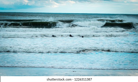 Ogunquit, Maine USA: November 10th 2018: Three surfers paddle through the rough shore break caused by huge ocean waves.