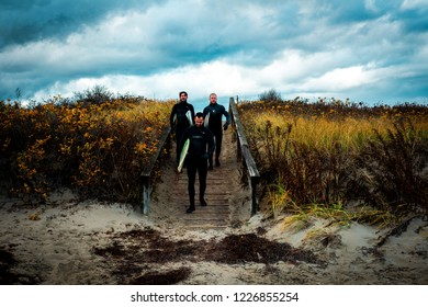 Ogunquit, Maine USA: November 10th 2018: three surfers cross over a wooden footbridge that crosses over sand dunes dressed in wetsuits and holding surfer boards on their way to the ocean.