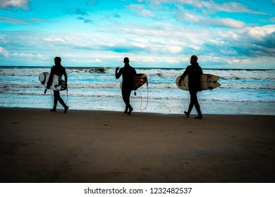 Ogunquit, Maine, USA: November 7th, 2018:  Three surfers silhouetted against a cloudy blue sky walking along the tide line looking at stormy ocean swells.