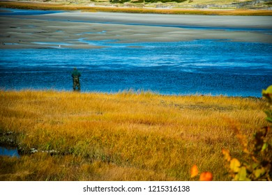 Ogunquit, Maine, USA: October 21st, 2018: A fly fisherman cast his line from the banks of the Ogunquit River at low tide on a sunny Fall day.