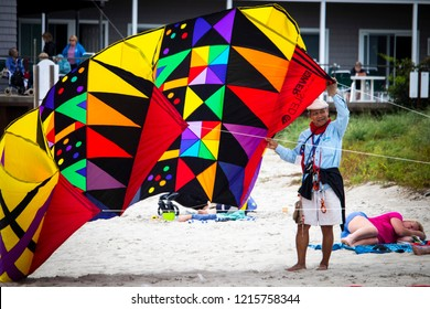 Ogunquit, Maine, USA: September 18th, 2018: A man standing on the beach prepares to fly his colorful oversized kite during the annual Ogunquit Kite Festival.