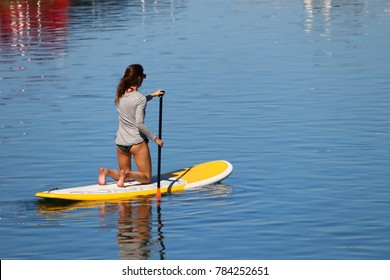 Ogunquit, Maine, USA-August 10, 2017: A young women is kneeling on her paddle board while paddling down the river in summer.