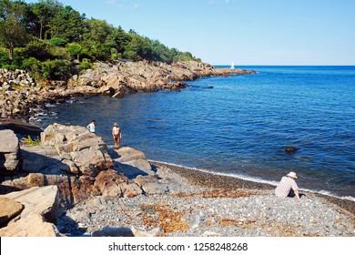 Ogunquit, ME, USA August 12, 2013 Several folks enjoy relaxing on the rocky shores near Ogunquit, Maine