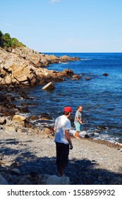 Ogunquit, ME, USA August 12, 2013 Two people stand at the edge of a rocky shore along the coast in Ogunquit, Maine