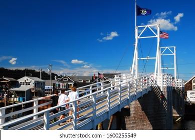 Ogunquit, ME, USA August 12, A family crosses a pedestrian draw bridge that crosses Perkins Cove in Ogunquit, Maine