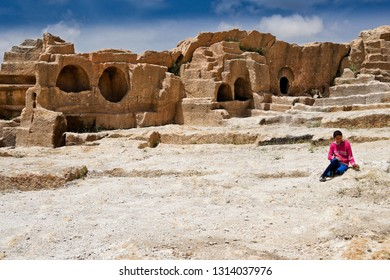 OGUZ, TURKEY — MAY 4, 2011. A girl in brightly colored clothes sits amid the ruins of the ancient fortress city of Dara in Eastern Anatolia on a sunny day.