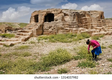 OGUZ, TURKEY — MAY 4, 2011. A girl in brightly colored clothes picks wildflowers amid the ruins of the ancient fortress city of Dara in Eastern Anatolia on a sunny day.