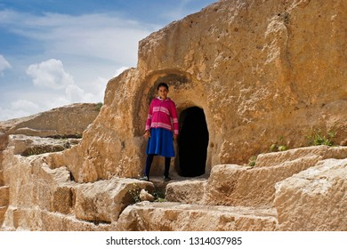 OGUZ, TURKEY — MAY 4, 2011. A girl in brightly colored clothes stands in the doorway of a home in the ruined ancient fortress city of Dara in Eastern Anatolia on a sunny day.