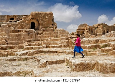 OGUZ, TURKEY — MAY 4, 2011. A girl in brightly colored clothes walks amid the ruins of the ancient fortress city of Dara in Eastern Anatolia on a sunny day.