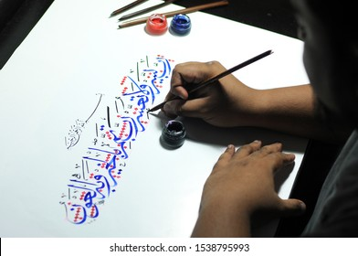 """Oh Allah, make this task easy and do not make it difficult. Oh Allah! Make it end well"" - Translation Arabic Calligraphy 			 			A Man Writing Arabic Calligraphy on White Paper using red and blue ink."