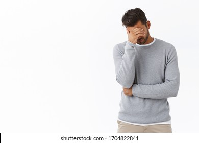 Oh god why me, so lame. Exhausted and bothered handsome male model in grey sweater, make face palm, hiding eyes with palm, bend head down frustrated and upset, humiliated or embarrassed