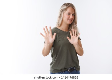 Oh gross take it away. Blond young woman grimacing from aversion step back of stinky disgusting thing raising hands in stop and no gesture, refusing and rejecting awful offer over white wall