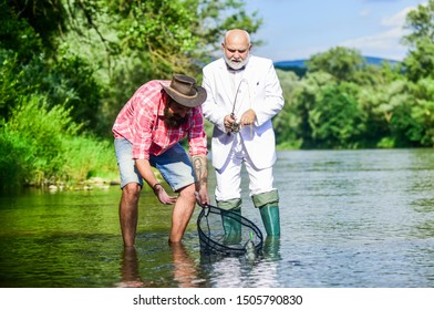 Oh happy day. Fishing team. Family day. Hobby and recreation. Freshwater fish. Bearded man and brutal hipster fishing. Catching fish with soulmate. Friends catching fish. Fish trapped in net.