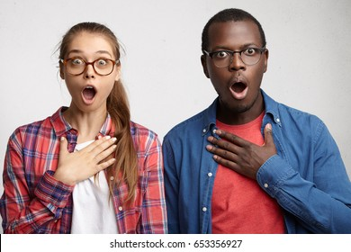 Oh my God! Caucasian woman in eyeglasses and checked shirt and Afro American guy staring at camera with opened eyes and mouth not believing their eyes what they see. Emotional mixed race people