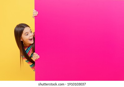 oh my god. child behind paper sheet. place for useful information. place for promotion and creativity. for your marketing design. surprised teen girl with paper banner. kid make announcement.