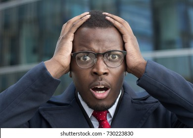 Oh my god! Closeup of young African American business man standing in street in city center looking shocked with eyes and mouth open, not able to believe in current situation