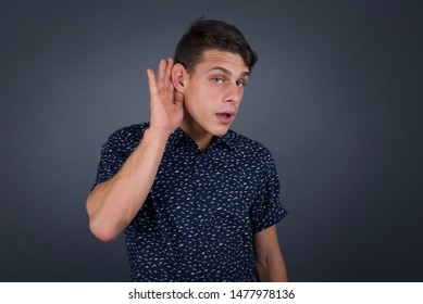 Oh my God! Funny astonished European male opening mouth widely, raising eyebrows and popping eyes out in surprise with hand near ear trying to listen to gossips.