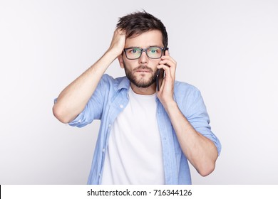 Oh my God. Human facial expressions, emotions, feelings. Bug-eyed stylish young office worker in glasses exclaiming in shock, keeping hand on head, astonished with some unexpected news by phone.