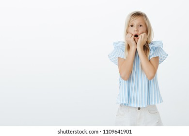 Oh my god, mom come and look. Curious amazed european little girl with fair hair, holding hands near opened mouth and staring focused at camera, watching tv and being shocked over gray wall