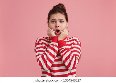 Oh my God! Photo of young female shocked worried, opened his mouth holds hands near the face and bites his nailsopened, looking at camera isolated over pink background.
