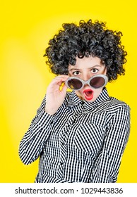 Oh my God! Shocked imposing girl with wide-open mouth and eyes staring at summer glasses on a yellow background