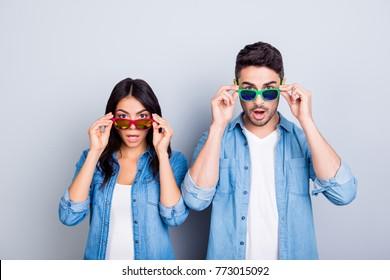 Oh my God! Shocked partners  with wide opened mouths and eyes peering out summer glasses  over grey background