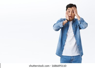 Oh my god what should I do. Shocked and concerned asian guy in panic grab his face and staring camera indecisive, standing alarmed got in terrible situation, have big problem, white background