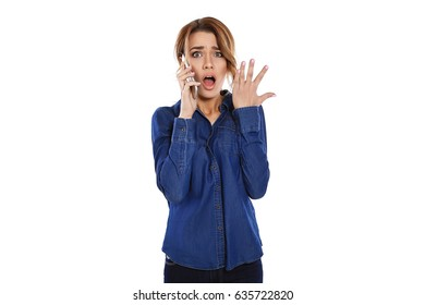 Oh no! Beautiful young woman talking on the phone looking at camera and looking shocked standing on white background