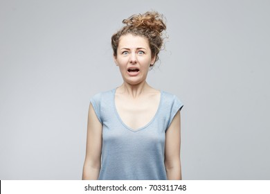 Oh no. Desperate stressed young attractive blue eyed woman looking at camera in terror and shock with her eyes popped out and opened mouth having worried and scared look. People and emotions concept.