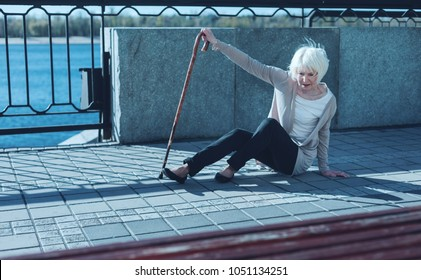 Oh no. Frightened retired woman leaning on a walking cane while trying to stand up after falling to the ground.