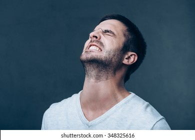 Oh no! Frustrated young man keeping eyes closed and expressing negativity while standing against grey background