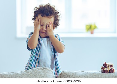 Oh no! Little African baby boy crying and rubbing his eyes while standing on the couch at home