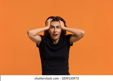 Oh no, my car was stolen. Portrait of shocked caucasian woman in black t-shirt looking at the camera in surprise, holding hands on head, sees something incredible bad. Isolated on an orange background