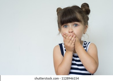 Oh no! Terrified shocked child with bugged eyes covers mouth with hands. Copy space.