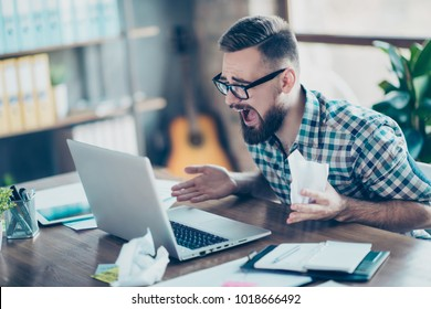 Oh no! It's unbeliveable! Angry frustrated tired unhappy surprised office worker wearing a checkered shirt sitting at the table in front of computer screen, he is holding crumpled documents