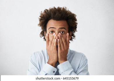 Oh no. Worried Afro American businessman covering face with both hands, feeling stressed out after his secretary accidentlly deleted all files on computer, looking at camera through his fingers