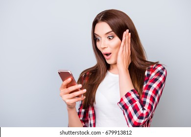 Oh no! Really?! Young astonished brunette lady standing on the pure light blue background, reading news at her mobile phone, wearing casual checkered shirt