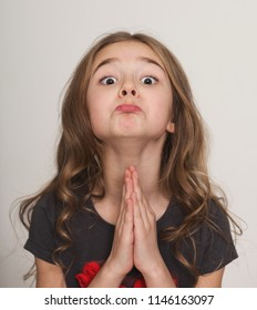 Oh please, may I please. Cute little girl pleading with hands clasped together, with funny grimace