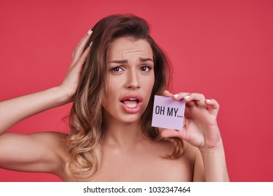 Oh my?  Shocked young woman looking at camera and keeping hand in hair while standing against pink background