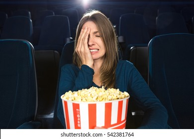 Oh snap! Woman looking frustrated and disappointed making facepalm while watching a movie alone at the cinema facepalm expressive annoyed disappointed emotional drama entertainment alone concept