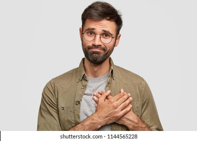 Oh, thank you very much! Attractive unshaven young male keeps hands on heart, expresses gratitude, stands against white studio wall. Friendly bearded Caucasian guy being thankful to best friend